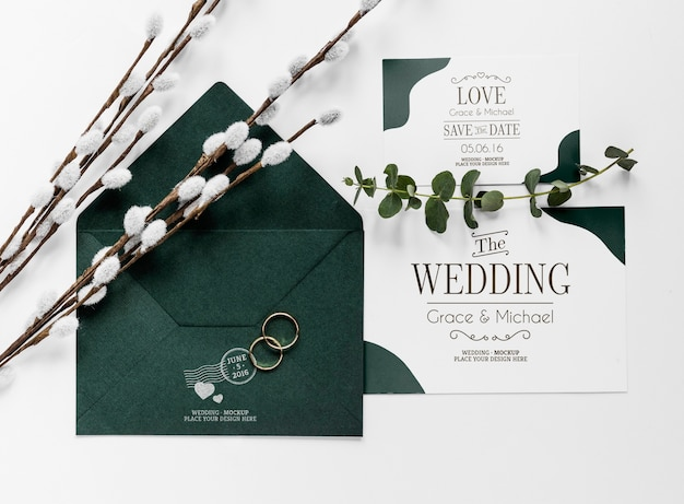Bovenaanzicht van bruiloft kaarten met envelop en ringen