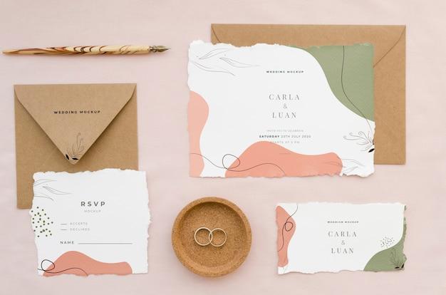 Bovenaanzicht van bruiloft kaarten met enveloppen en ringen