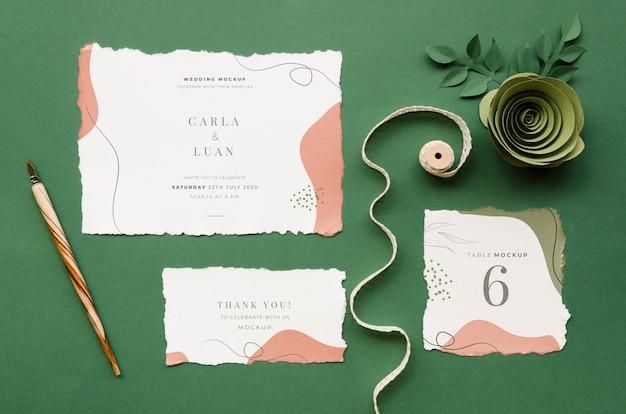 Bovenaanzicht van bruiloft kaarten met papier roos en lint