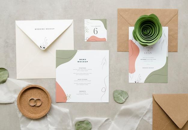 Bovenaanzicht van bruiloft kaarten met papier roos en textiel