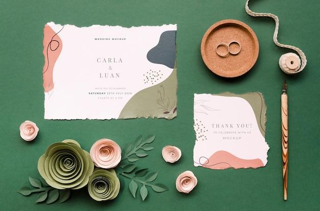 Bovenaanzicht van bruiloft kaarten met papieren rozen en ringen