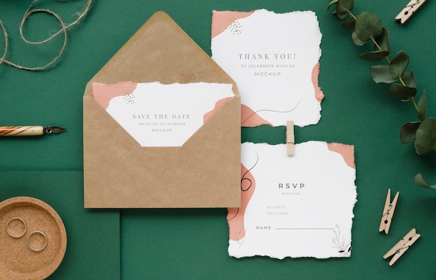 Bovenaanzicht van bruiloft kaarten met plant en kleding pinnen