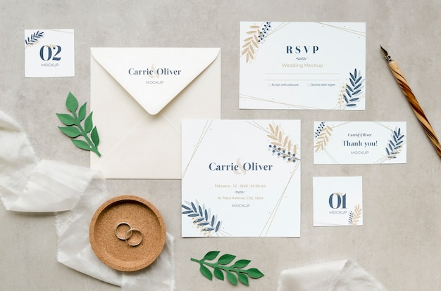 Bovenaanzicht van bruiloft kaarten met ringen en bladeren