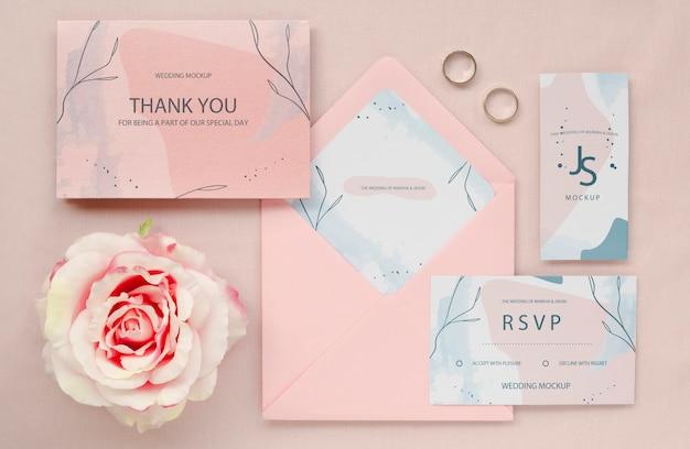 Bovenaanzicht van bruiloft kaarten met roos en ringen