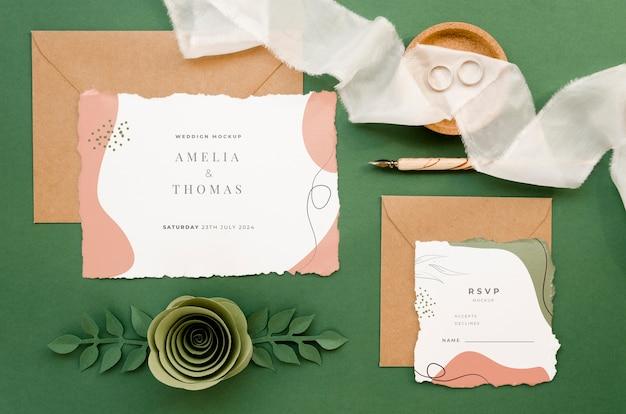Bovenaanzicht van bruiloft kaarten met rozen en papier steeg