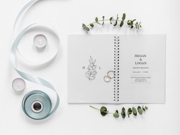Bovenaanzicht van bruiloft notebook met lint en ringen