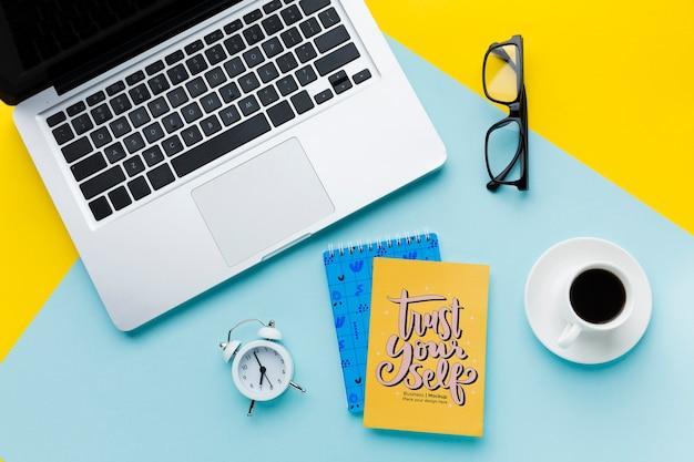 Bovenaanzicht van bureau met laptop en klok