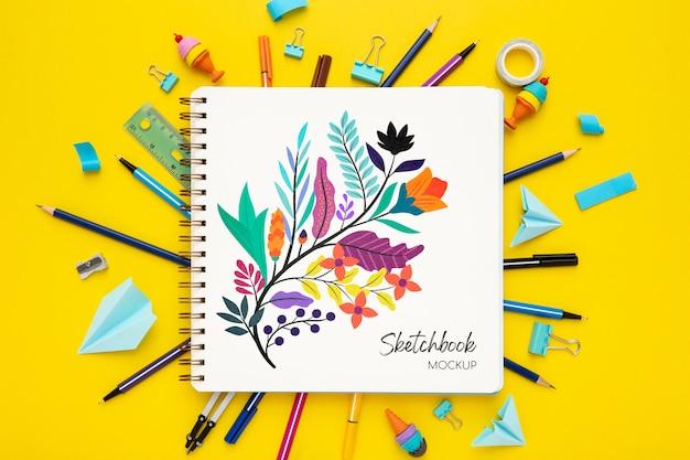 Bovenaanzicht van bureau oppervlak met notebook en kleurrijke pennen