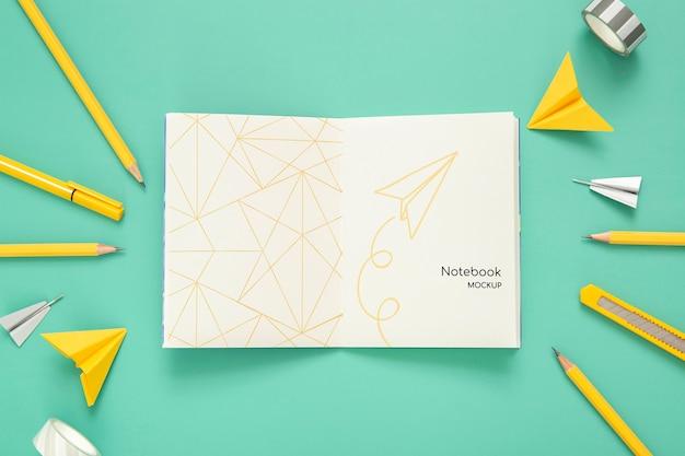 Bovenaanzicht van bureau oppervlak met potloden en papieren vliegtuigen