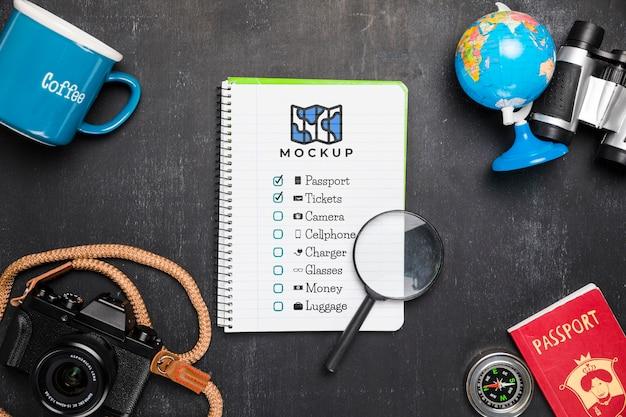 Bovenaanzicht van checklist met vergrootglas en camera voor op reis