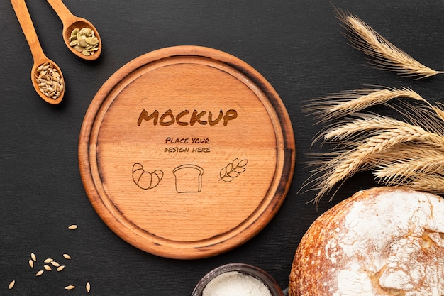 Bovenaanzicht van een houten bord met brood en tarwe