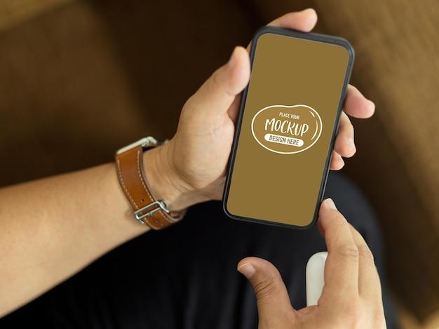 Bovenaanzicht van een man zittend op de bank en smartphone mockup te houden