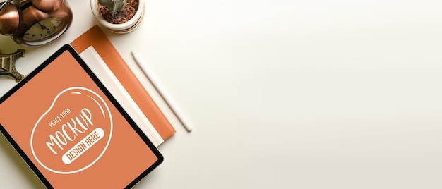 Bovenaanzicht van eenvoudige studeertafel met mockup voor digitale tablet, briefpapier en decoraties