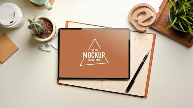 Bovenaanzicht van eenvoudige studeertafel met mockup voor digitale tablet en briefpapier