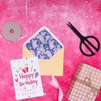 Bovenaanzicht van envelop met cadeau en lint