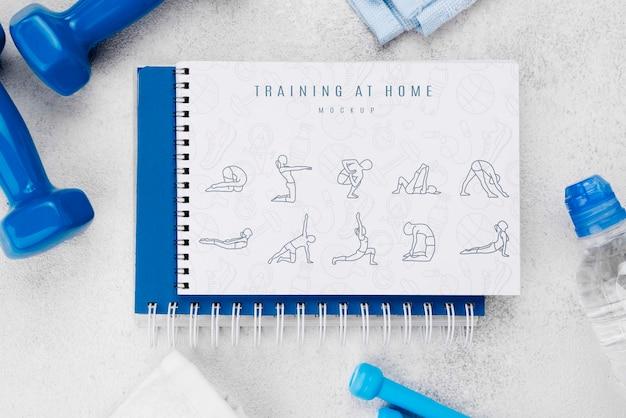Bovenaanzicht van fitness notebook met gewichten en fles water