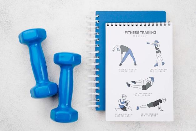 Bovenaanzicht van fitness notebook met gewichten