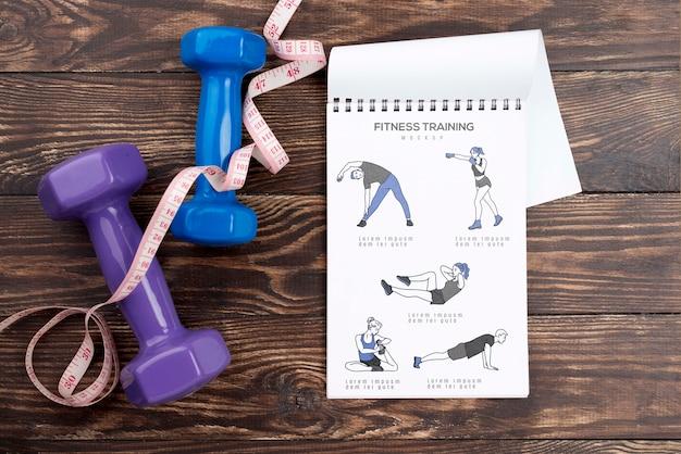 Bovenaanzicht van fitness notebook met meetlint en gewichten