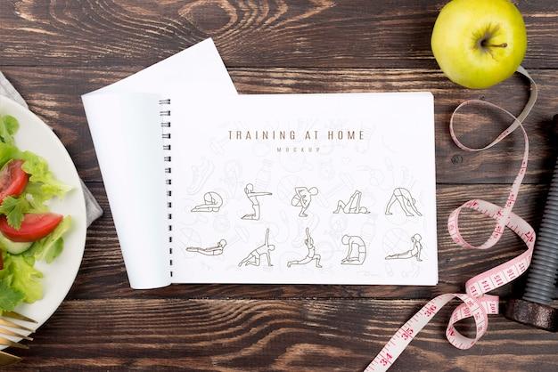 Bovenaanzicht van fitness notebook met plaat van salade en appel