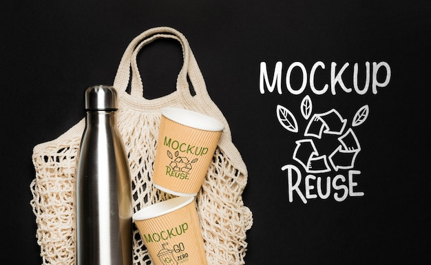 Bovenaanzicht van fles met papieren bekers en herbruikbare tas