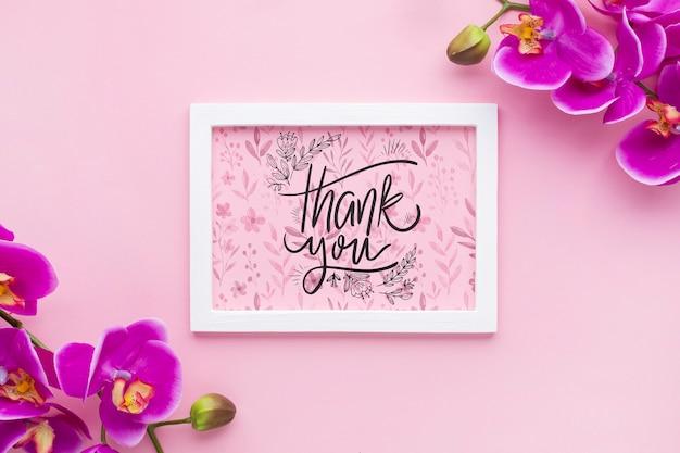 Bovenaanzicht van frame mock-up en bloemen op roze achtergrond