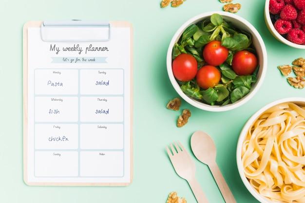 Bovenaanzicht van geplande maaltijden met kommen en notitieblok