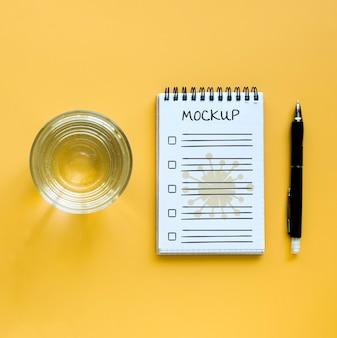 Bovenaanzicht van glas water met notitieboekje en pen