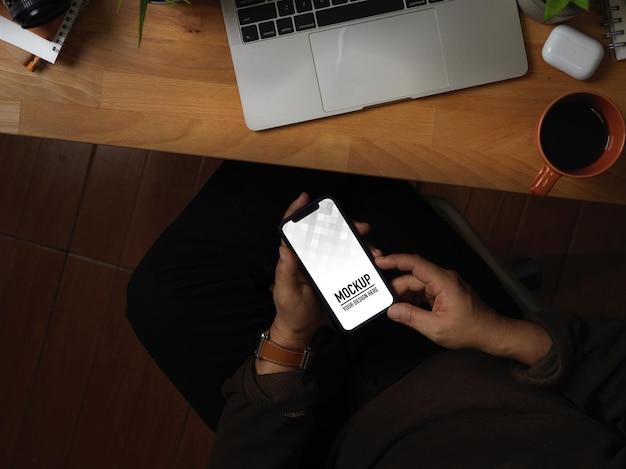 Bovenaanzicht van handen met behulp van smartphonemodel