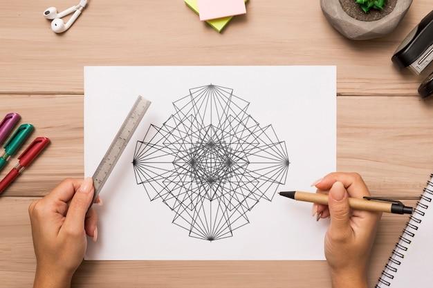 Bovenaanzicht van handen tekenen op bureau