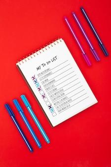 Bovenaanzicht van het bureau oppervlak met takenlijst en pennen