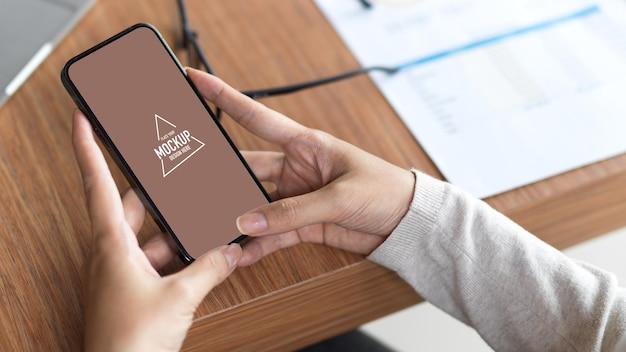 Bovenaanzicht van het lege scherm van de mobiele telefoon met twee handen op het houten bureau