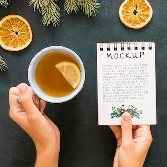 Bovenaanzicht van houder van kladblok met thee