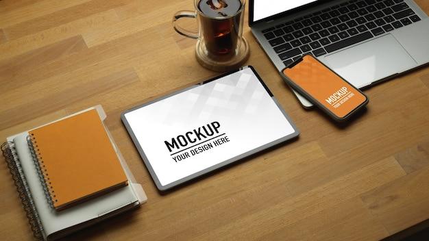 Bovenaanzicht van houten tafel met mockup voor tablet en smartphone