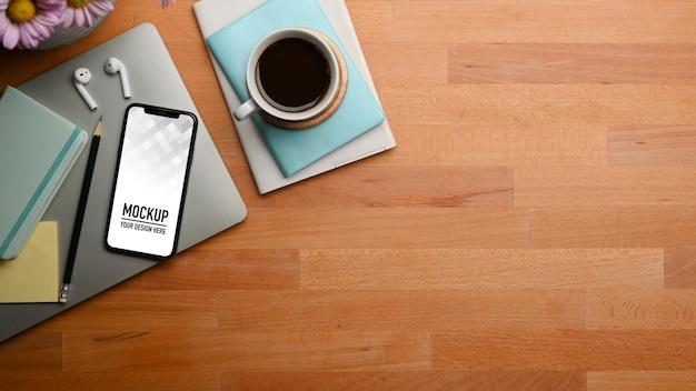Bovenaanzicht van houten tafel met smartphone en briefpapier, laptop, koffiekopje