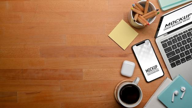 Bovenaanzicht van houten tafel met smartphone, laptop, briefpapier, accessoires