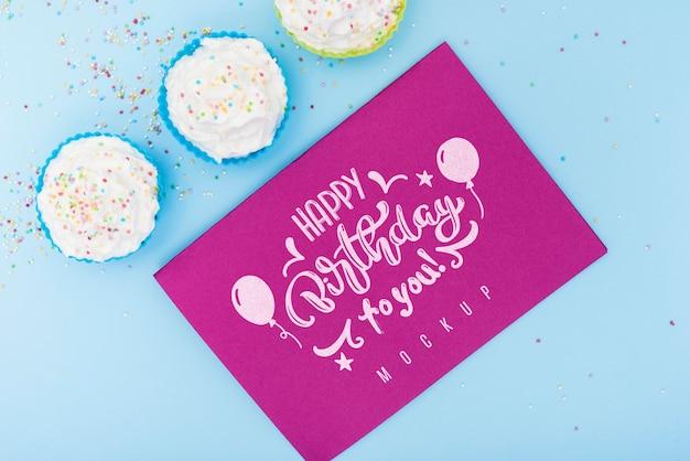 Bovenaanzicht van kaart met gelukkige verjaardag en cupcakes