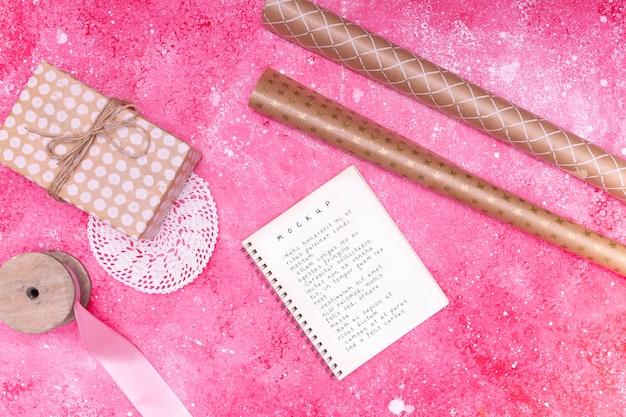 Bovenaanzicht van kladblok met cadeau en lint