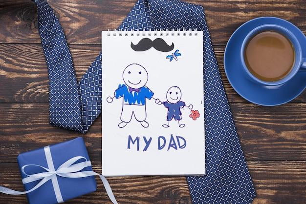 Bovenaanzicht van kladblok met stropdas en koffie voor vaderdag
