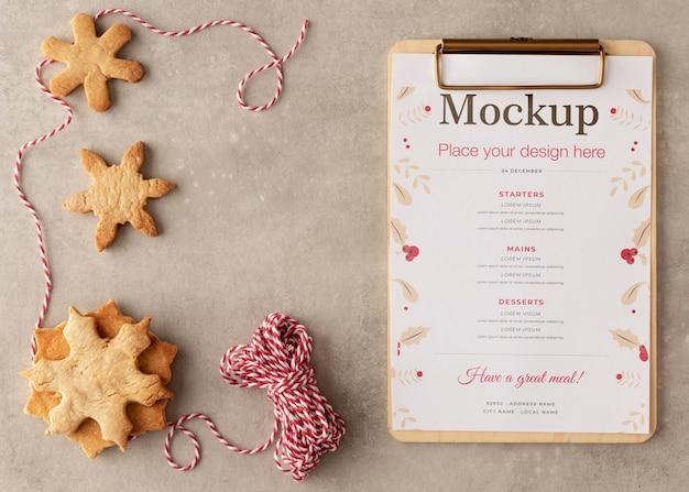 Bovenaanzicht van klembord met sneeuwvlok cookies en string