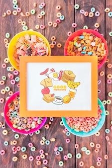 Bovenaanzicht van kleurrijke ceareals met frame mockup op houten tafel