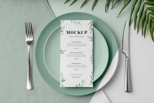 Bovenaanzicht van lentemenu mock-up op borden met bladeren en bestek