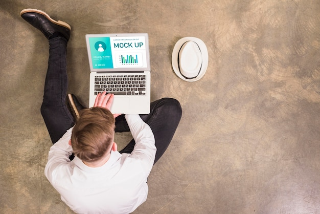 Bovenaanzicht van man aan het werk op laptop met kopie ruimte