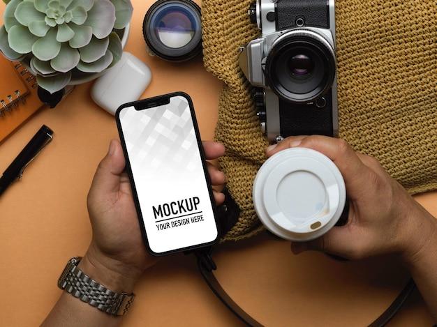 Bovenaanzicht van mannelijke hand met smartphone mockup