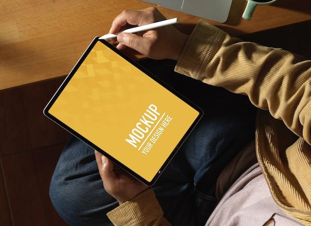 Bovenaanzicht van mannelijke handen met behulp van digitale tablet mockup zittend op de werkplek
