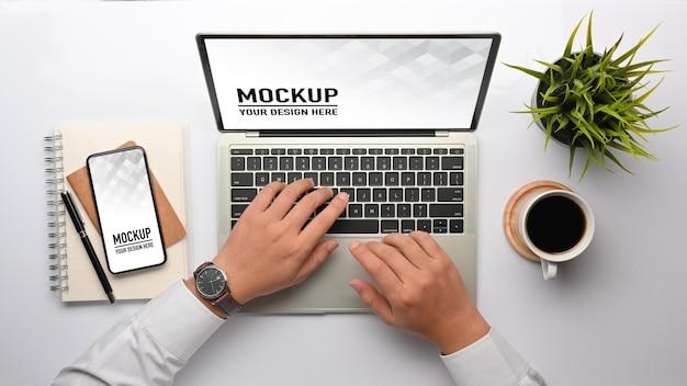 Bovenaanzicht van mannelijke handen typen op laptop mockup