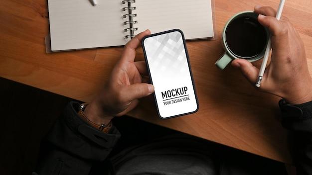 Bovenaanzicht van mannenhand met schemaboek en koffiekopje met telefoonmodel