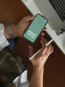 Bovenaanzicht van mannenhand met smartphone omvatten uitknippad terwijl styluspen vastgehouden