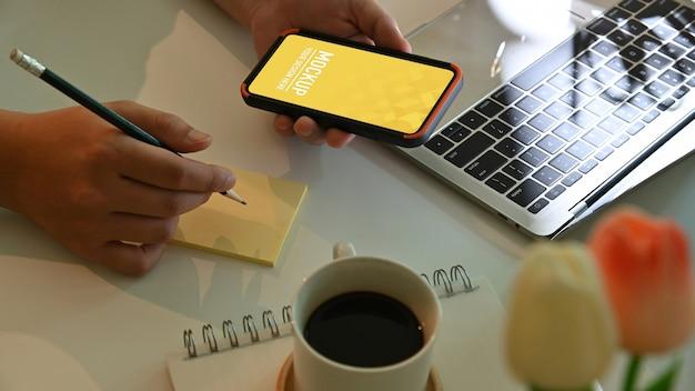 Bovenaanzicht van mannenhand smartphone mockup houden en nota nemen