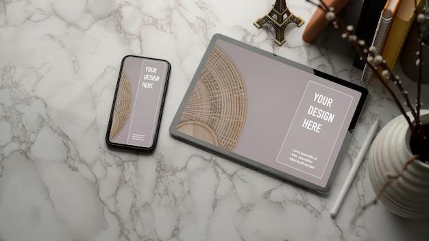Bovenaanzicht van marmeren werktafel met mock-up tablet, smartphone, boeken en kopieerruimte