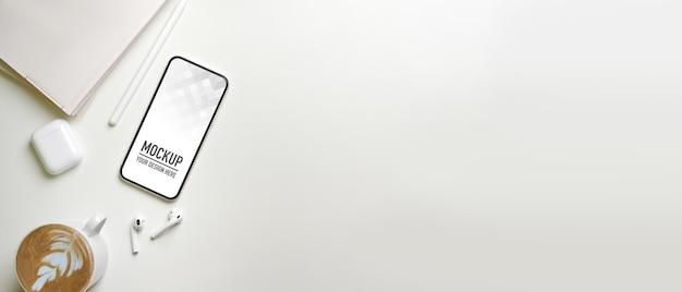Bovenaanzicht van minimale werkruimte met smartphonemodel, oortelefoon, notebook en koffie